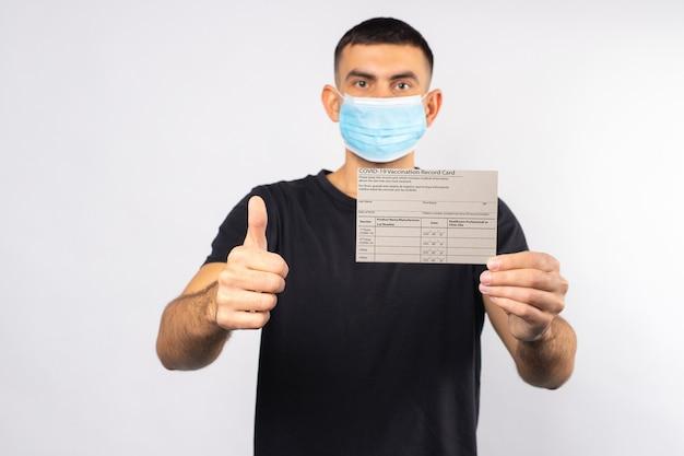 의료용 마스크로 격리 중 안전한 남자가 코로나 바이러스 예방 접종 카드를 들고