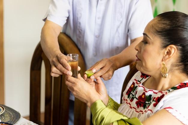 自宅でメキシコのテキーラのショットを妻に提供している男性