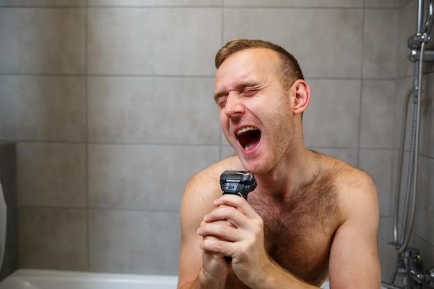 男は鏡の前で電気かみそりで顔を剃る。皮膚の炎症。入浴手順