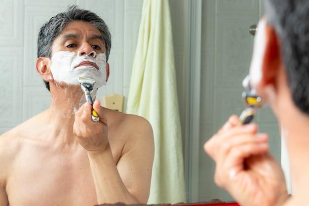 トイレで顔を剃っている男