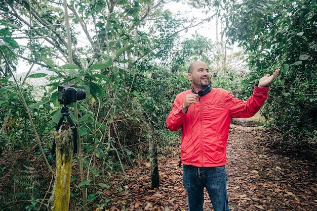 마이크에 대고 말하면서 비디오를 녹화하는 자연 환경을 보여주는 남자
