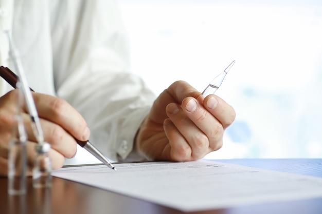 男性が医療文書に署名します。テーブルの上の医療機器。聴診器と注射器付きアンプル。オフィスでメモを取ります。医療センター。