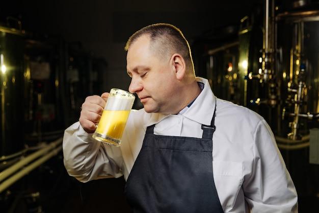 背の高いグラスビールをすすりながら男。唇とビールに焦点を当てた浅い被写界深度。