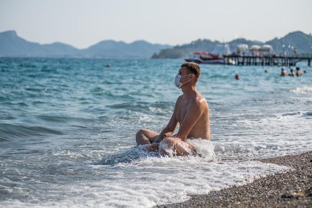 19インフルエンザの流行の間、男は一人で海とマスクに座ります
