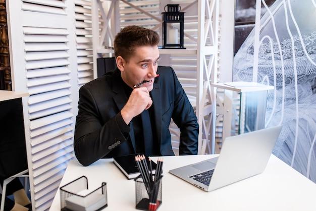 Мужчина сидит за ноутбуком и удивляется, когда держит во рту карандаш