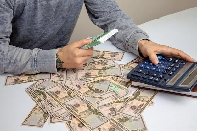 男はドルでお金が山積みされたテーブルに座って、電卓でお金を数えます