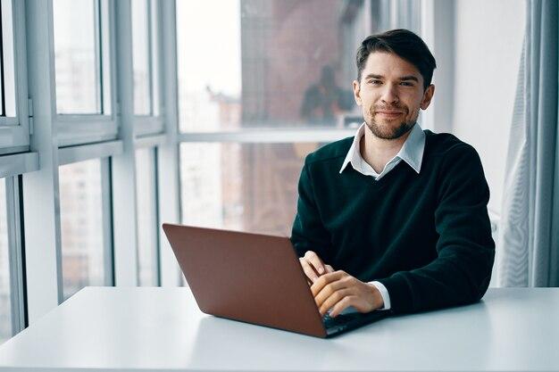 インターネットを介して作業しているラップトップの前のテーブルに座っている男性