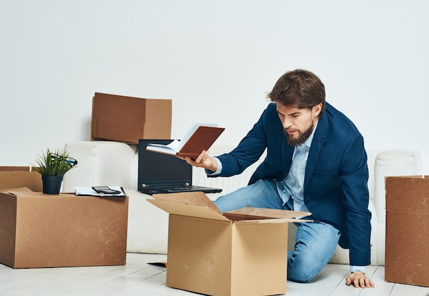 한 남자가 새로운 직업의 포장을 풀고있는 상자에 앉아 있습니다. 고품질 사진