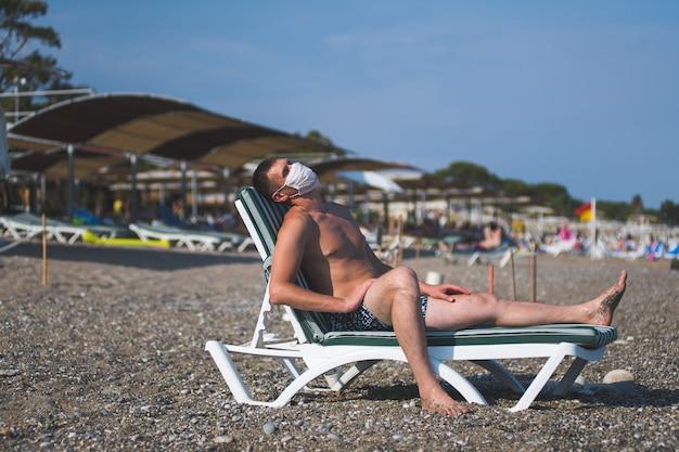 19インフルエンザの流行の最中、ビーチで一人でマスクをかぶった男がデッキチェアに座る