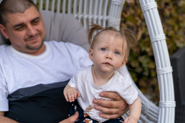 Мужчина сидит в большом белом стуле и держит на руках годовалую дочь.