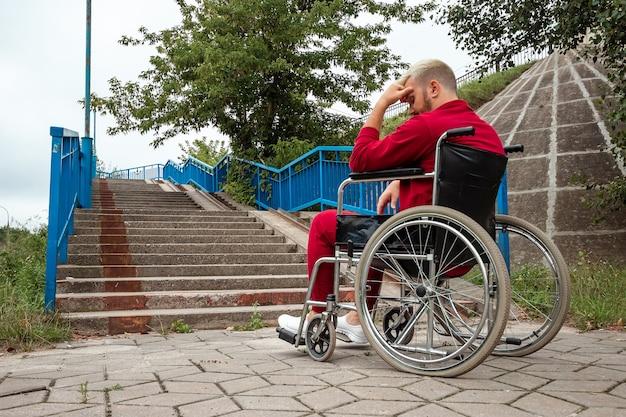 男は車椅子に座り、一人で困難に直面し、うつ病になります。車椅子、障害者、フルライフ、麻痺、障害者、ヘルスケアの概念。