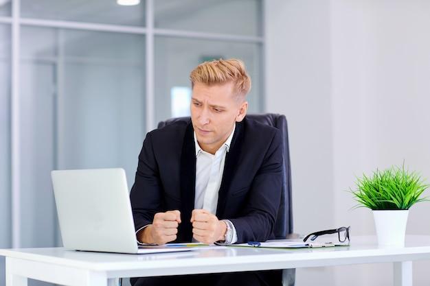 男は彼の机で金髪の欲求不満のラップトップの前に座っています