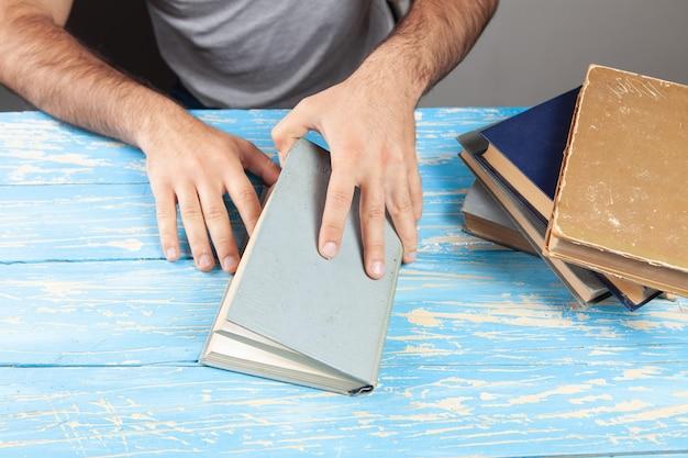 한 남자가 책 앞에 앉아 책을 펼칩니다.
