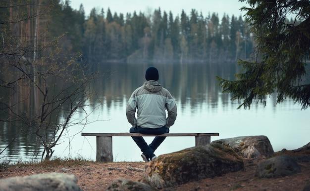 남자는 숲의 호수 근처 벤치에 앉아있다. 뒤에서 봅니다.