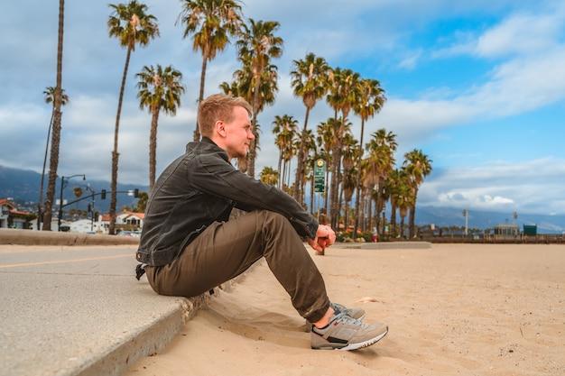 サンタバーバラカリフォルニアのヤシの木に沿って遊歩道に座っている男