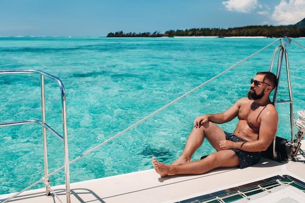 한 남자가 열대 모리셔스 섬 근처 인도양의 쌍동선에 앉아 있습니다. 산호초.