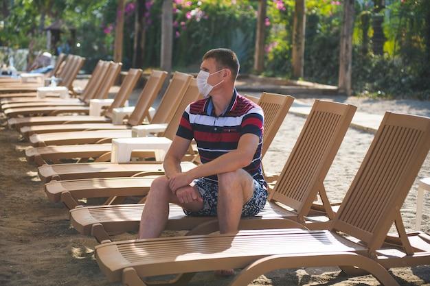 19インフルエンザの流行中、ビーチで一人でマスクをしたデッキチェアに座っている男性