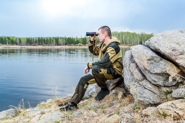 Мужчина сидит на камне у озера и смотрит в бинокль