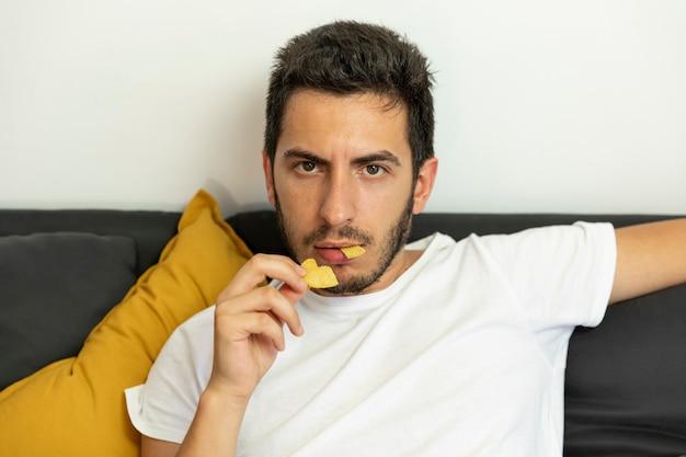 Мужчина сидит на диване и ест чипсы.