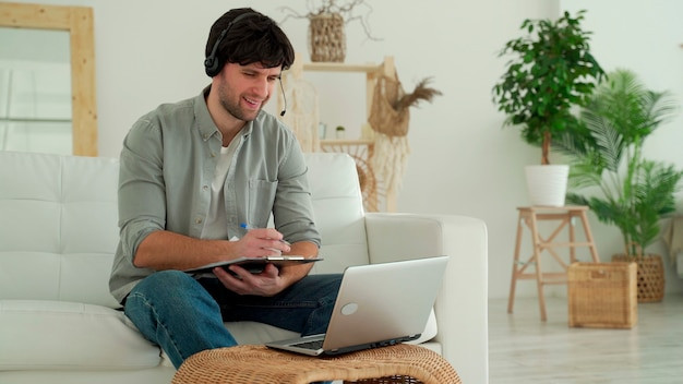 家の居間のソファにノートパソコンとヘッドセットを持って座っている男性が、ビデオリンクを介して通信している