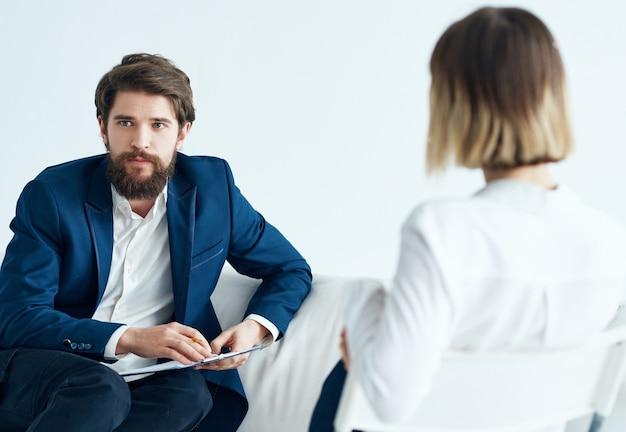 Мужчина сидит на диване рядом с пациентом, который посещает психологическую терапию. фото высокого качества
