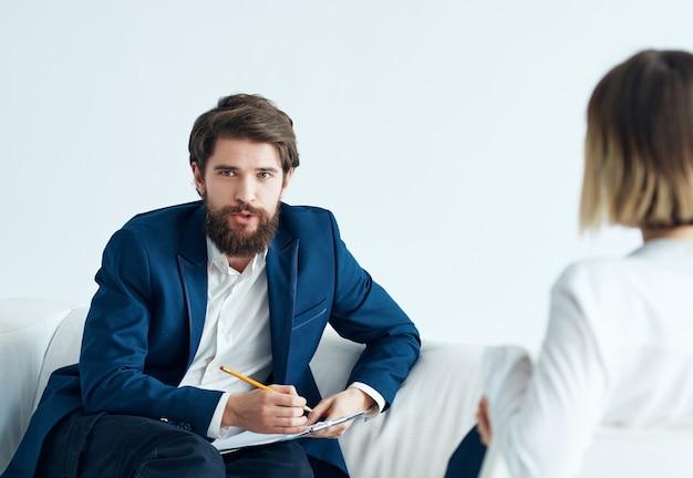 Мужчина сидит на диване рядом с пациентом, посещающим психолога.
