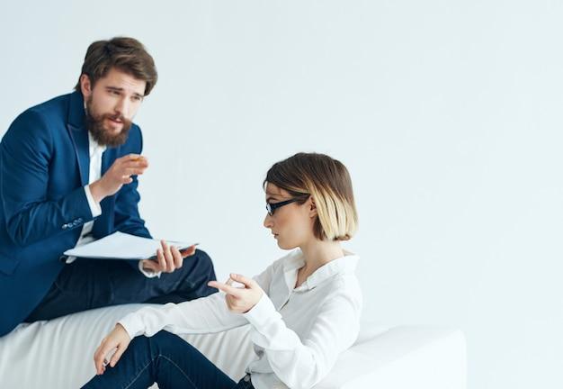 男性は女性のコミュニケーションチームのパートナーの隣のソファに座っています