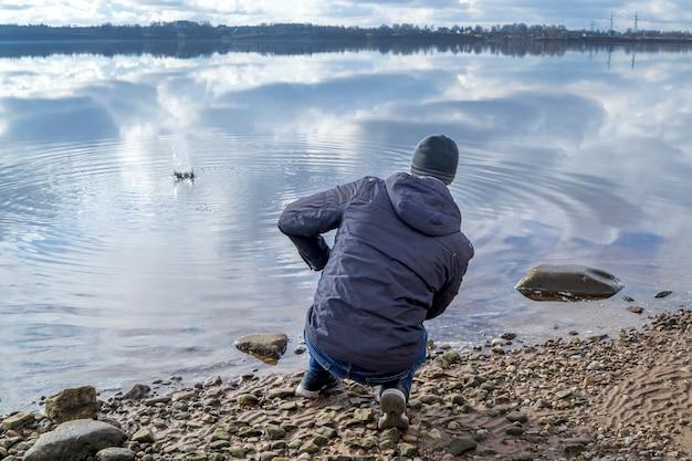 川の土手に座って石を水に投げ込む男