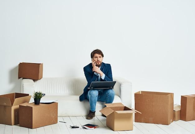 ラップトップの作業ボックスの前のソファに座って、新しいオフィスを開梱するものを持っている男性。