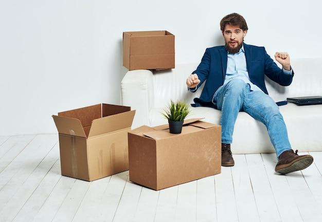 한 남자가 새로운 이동 위치를 풀고 상자 옆에있는 소파에 앉아있다