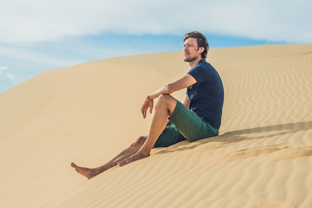 男は砂漠の砂の上に座っています