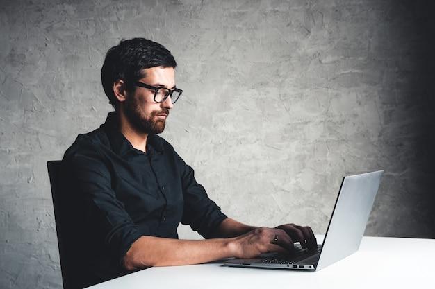 男は黒いシャツを着たラップトップを持って座っています。ビジネスコンセプト、仕事。オフィスルーチン。財産の取り組み