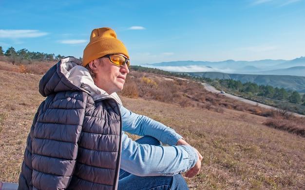 山の高いところに目を閉じて座っている男が休んでいる