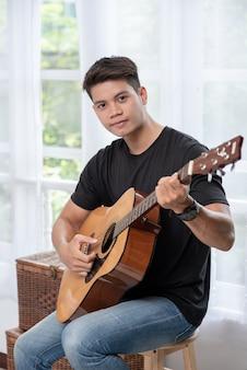 Человек сидит и играет на гитаре на стуле.