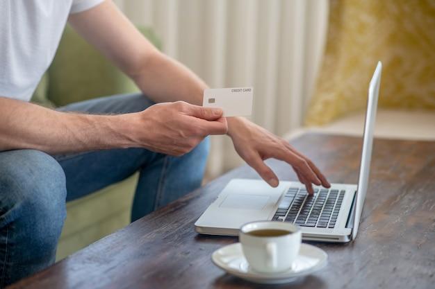 Мужчина сидит за ноутбуком и расплачивается кредитной картой онлайн
