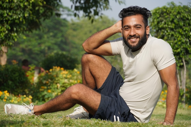 公園に座ってカジュアルな服装でポーズをとる男性