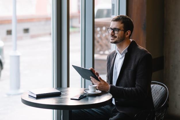 Мужчина сидит в кафе с планшетом