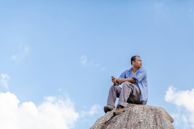 青い空を背景に岩の上に座っている男