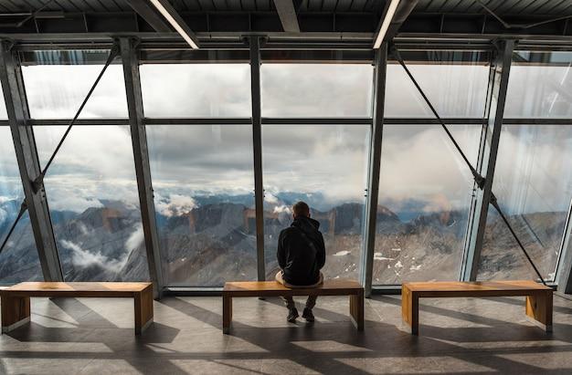 Мужчина сидит на смотровой площадке на горе цугшпитце