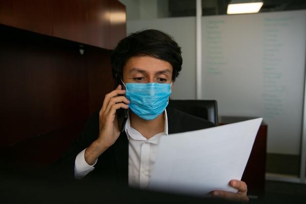 바이러스 예방을 위해 보호 마스크를 쓰고 전화 통화를하는 남자