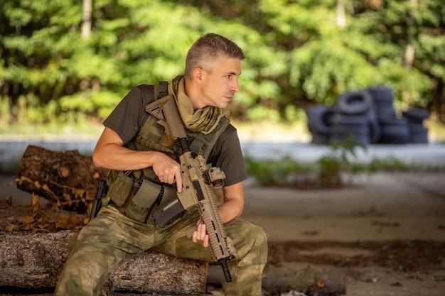 コンクリート格納庫の軍服でエアガンアサルトライフルと一緒に座っている男