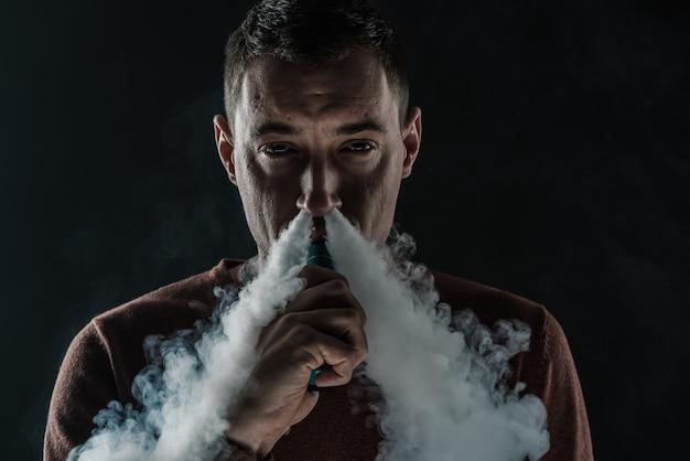 Мужчина курит vape на черном фоне белый дым паровой портрет крупным планом. фото высокого качества
