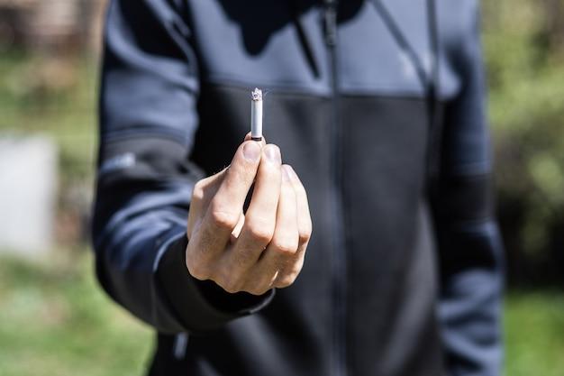 日中、男が公園で煙草を吸う
