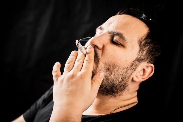 담배나 마약을 피우는 남자는 중독과 돈 공포의 개념인 압연 달러입니다