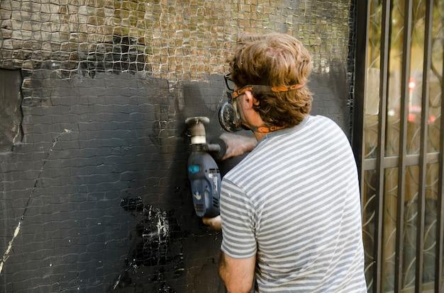 보호 마스크를 쓴 벽 그라인더로 벽면을 매끄럽게 하는 남자