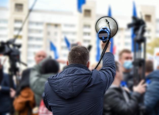 Мужчина говорит через громкоговоритель на митинге.