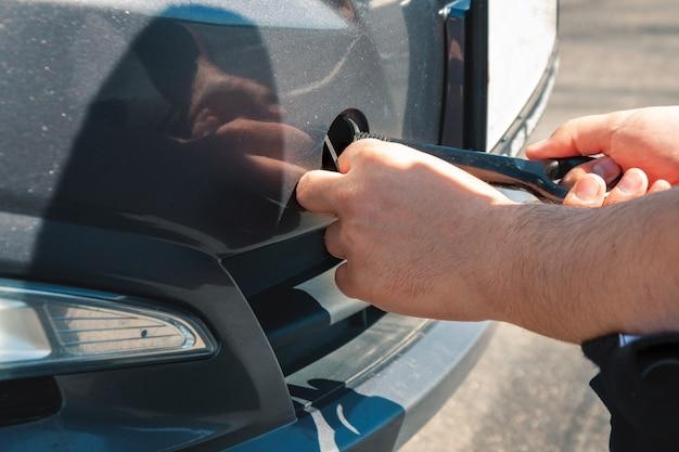 Мужчина крутит крюк для буксировки перед автомобилем. поломка машины и эвакуация.