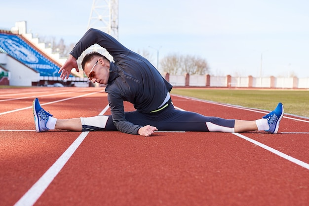 男のスポーツマンがスタジアムの陸上競技場で横方向のより糸を実行します