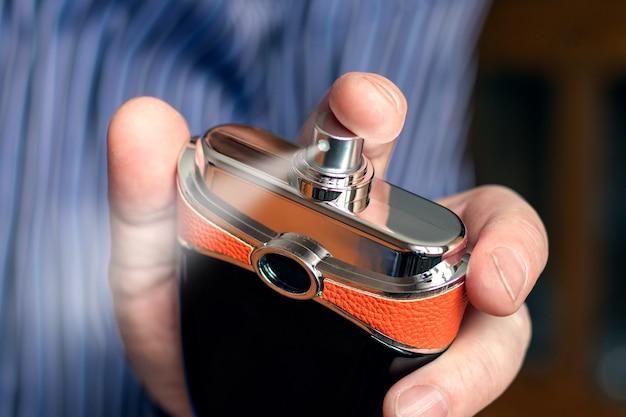 男性が香水をスプレーし、男性の手に香水をスプレーします