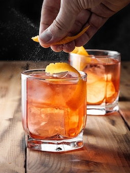 男はネグローニカクテルでグラスの上にオレンジの熱意を絞ります。縦の写真。